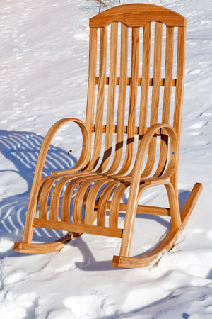 elbow chair: Wooden rocking chair in the snow. Winter sunny day. Stock Photo