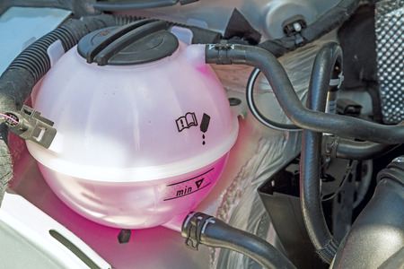 Coolant Tank with pink antifreeze in the engine Stock Photo