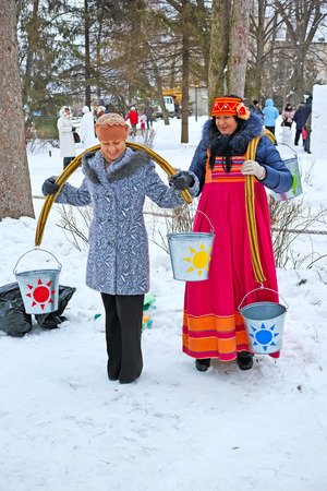 Tambov, Russia - February 15, 2015: Maslenitsa (pancake week, shrovetide) - carnival of farewell winter and meeting spring in Tambov.  Women with rockers carrying buckets of water.  The quality of medium format