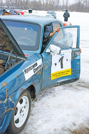 rectify: Tambov, Russia - 21 febbraio 2015: gare in pista auto inverno sulla tazza della regione di Tambov. Pilot Sergei Krasnov rettificare sgualcito portiera della macchina. La qualit� del medio formato