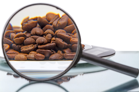 Coffee beans on electronic scales and magnifier photo
