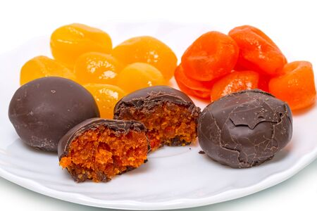 cumquat: Dry yellow and orange cumquat and chocolate candies on a white plate