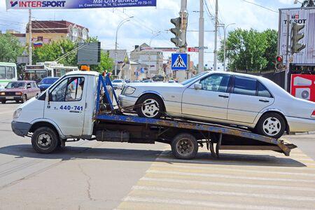 Tambov, Russland - 18. Juni 2014: Gazelle Abschleppwagen tragen ein kaputtes Auto an der Kreuzung der Stadt. Umzugservice Fahrzeug bei einem Unfall oder unsachgemäße Parkplatz. Urban-Szene an einem sonnigen Sommertag