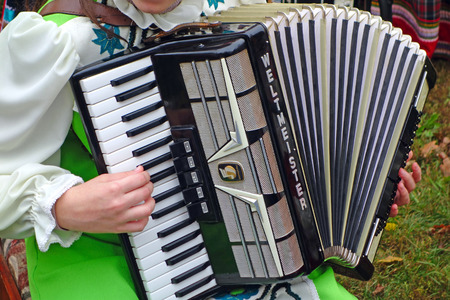 Tambov, Russia - October 12, 2013: a female folk accordionist playing a piano accordion  on fair. The Weltmeister accordion  from the German town Klingenthal, famous throughout the world.