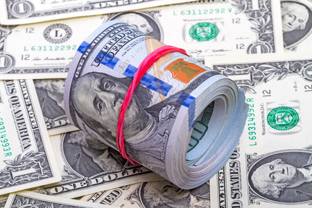 bankroll: Hundred dollar roll up with red rubber on dollars background Stock Photo