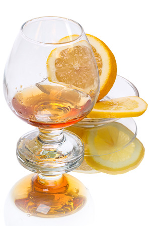 brandy: Cognac (brandy) glass and Lemon  isolated on white background