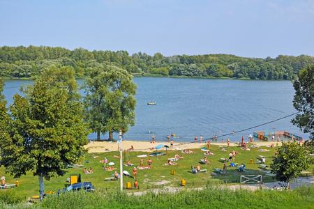 cna: Tambov, Rusia - 08 de agosto 2015: La gente se relaja en la pequeña playa de arena de Tambov. Ancho río Cna y el bosque a través del río en un día caluroso y soleado. La calidad de formato medio