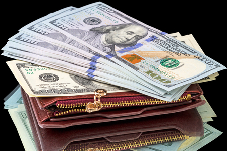 bankroll: One hundred dollar bills on a leather purse isolated on a black background