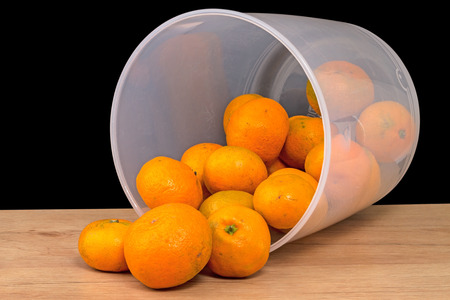 Overturned plastic bucket with bad not conditionally tangerines Stock Photo