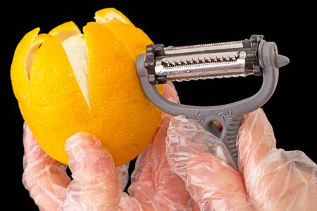 special steel: Hands in gloves transparent orange peel special stainless steel knife. Isolated on a black background