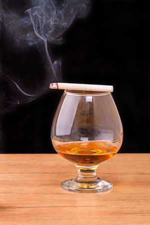 smoldering: Glass of Cognac (brandy) and smoking a cigarette isolated on black background Stock Photo
