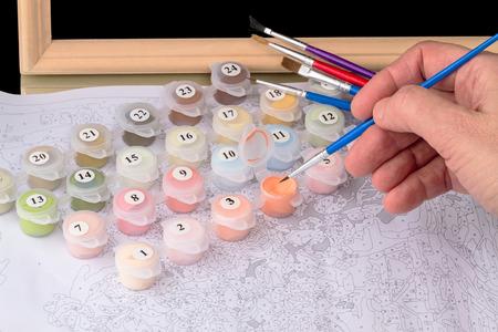Hand met een fijne penseel op canvas op nummer Stockfoto