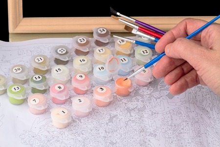 brush painting: Hand with a fine brush painting on canvas by numbers