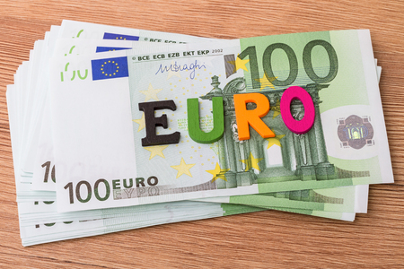 single word: Pack of bank notes hundred euros and Single word euro