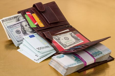 credit union: Wallet filled with paper money (dollars, euros, russian roubles)  and credit cards on a gold background Stock Photo