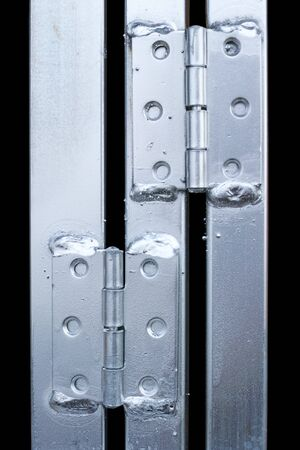 hinges: Galvanized hinges and metal profile isolated on a black background