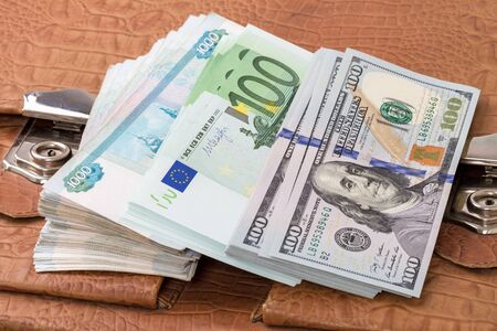 roubles: Pile of paper money (dollars, euros, russian roubles) on a yellow portfolio