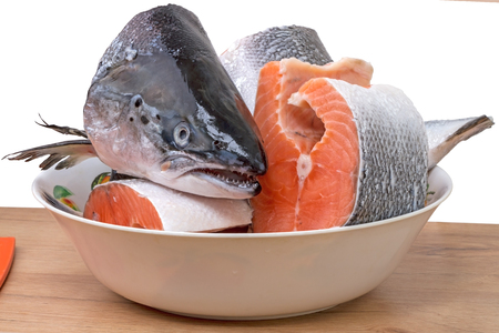 food state: Large pieces of fresh salmon in bowl on a white background