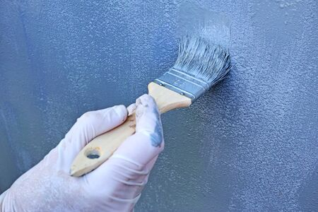 rubber glove: Hand in rubber glove brush paints a gray oil paint metal surface