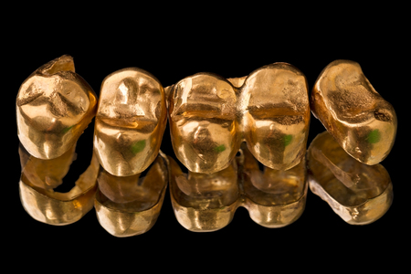 Gold dental crowns (prosthetic teeth) isolated on black background Stock Photo