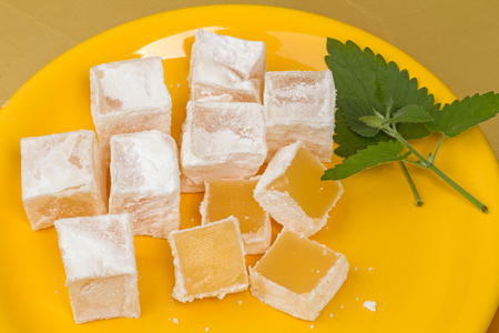 turkish ethnicity: Delight in powdered sugar on a yellow plate and mint leaves