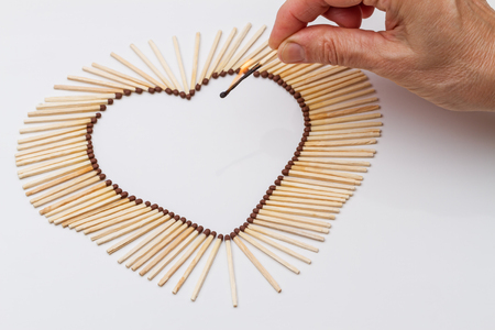 heart burn: Matches in the shape of a heart and a burning match in a hand on a white background