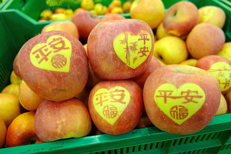 Japanese apples with hieroglyphs in a plastic box closeup Stock Photo