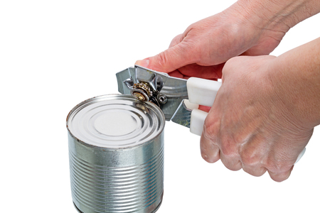 Hands open tin can opener mechanical. Isolated on white background. Stock Photo