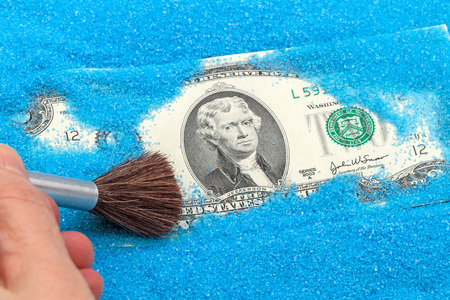 Two of the US dollar in the blue sand and brush