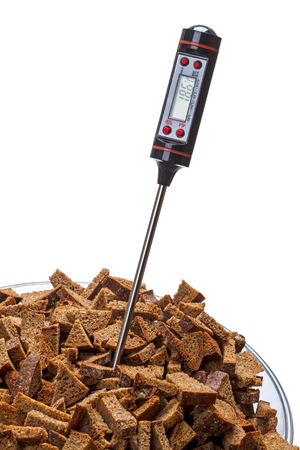 Convenient Digital Food Thermometer with LCD Display and rye biscuits. Isolated on white background