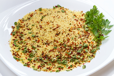 diameter: Couscous is a Maghrebi dish of small (about 3mm diameter) steamed balls of crushed durum wheat semolina, usually served with a stew spooned on top. Stock Photo