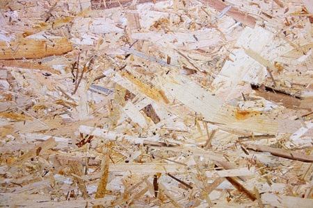 Oriented strand board (OSB), also known as flakeboard, sterling board and aspenite in British English, is a type of engineered lumber, similar to particle board, formed by adding adhesives and then compressing layers of wood strands (flakes) in specific orientations. Stock Photo