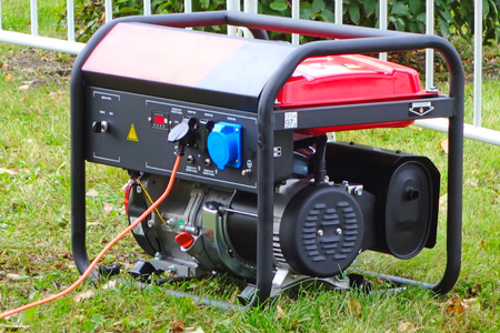Working portable electric generator on green grass