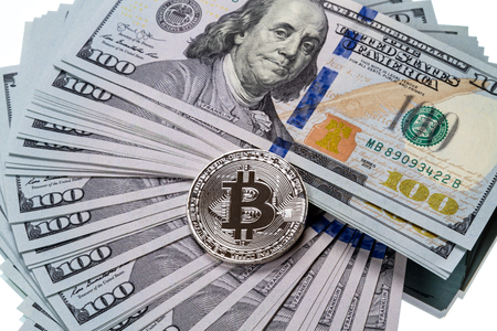 Silver bitcoin on a pile of dollars on a white background