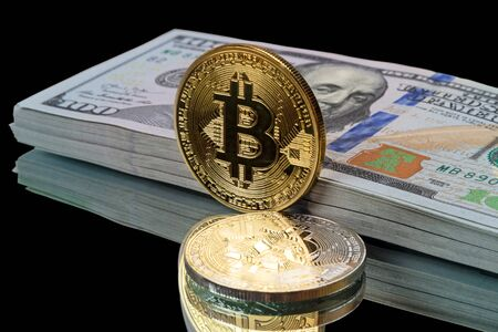 Gold and silver  bitcoin and a pack of dollar on a black background