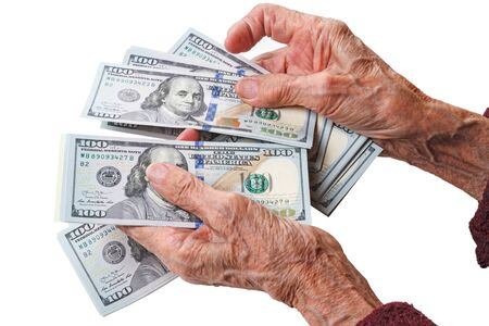 Wrinkled hands of an old woman counts one hundred dollar bills Stock Photo
