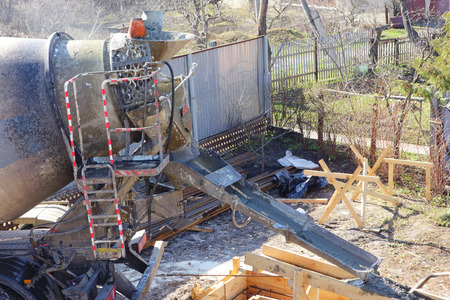 The concrete mixer machine pours concrete into the forms of the ribbon foundation