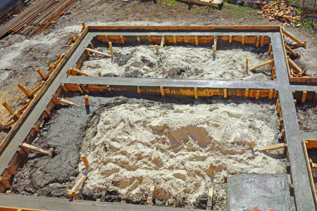 Liquid concrete is poured into the wooden form of the ribbon foundation