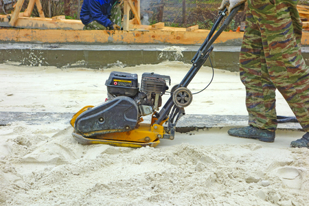 Working compacts sand with a gasoline plate compactor. People not recognizable