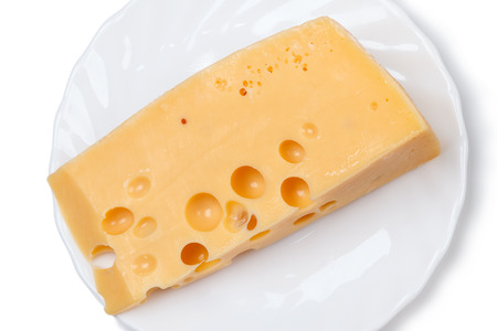 Piece of cheese on a white plate. Made from cows milk, it is aged for at least 4 weeks.