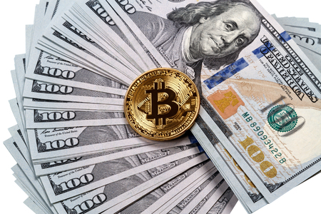 Gold bitcoin on a pile of dollars on a white background