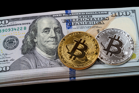 Gold and silver bitcoins on a pile of dollars on a black background Stock Photo