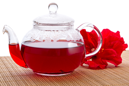 Transparent teapot with hot tea and hibiscus flower