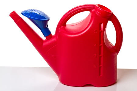 Red plastic watering can on пять liters on a white background