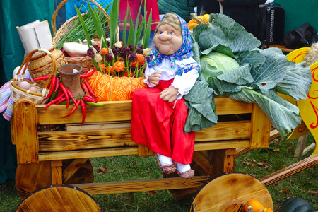 Grandma doll on a wooden cart with a harvest of vegetables