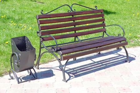 Bench made of forged metal and wood in the park and urn