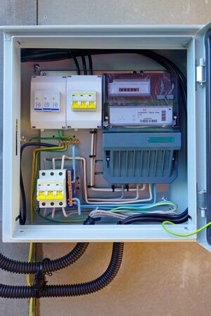 Introductory electrical box with three-phase electricity meter and circuit breakers. 스톡 콘텐츠