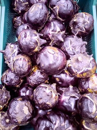 Round eggplants in a box. Nature background