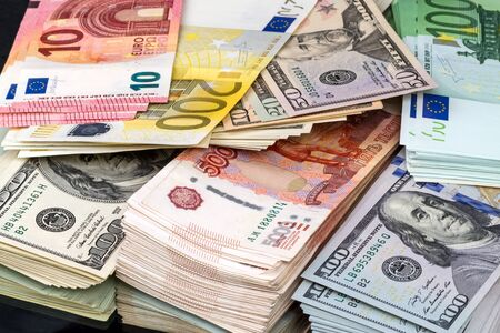 Bundles of money - Euro, Russian rubles and US dollars