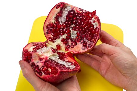 Two halves of a pomegranate in the hands on white background